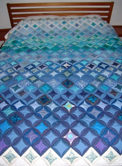 Bed cover with quilted diamonds in blues reminiscent of Hawaiian ocean