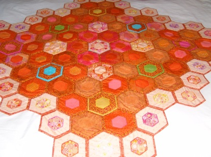 Sofa throw of quilted hexagons with embroidered centres